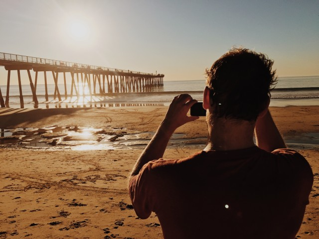 Man taking a phone with iphone at pier and beach