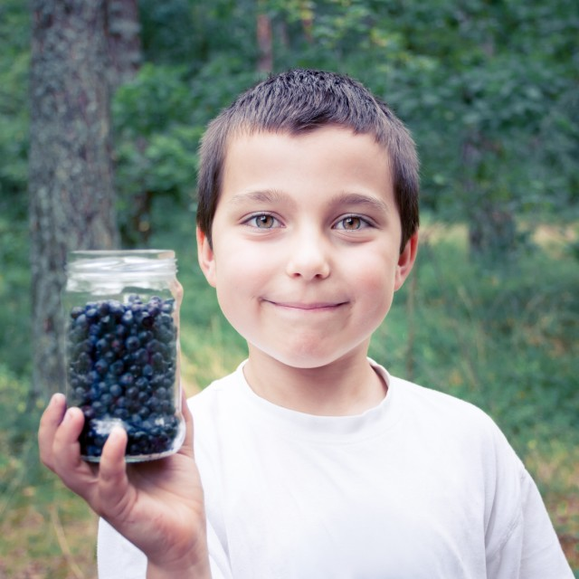Portrait of smiling boy showing jar full of blueberries standing in a forest