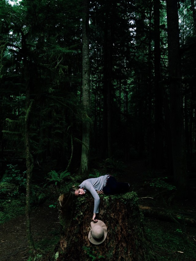 A girl lying on a miss stump in the rainforest.