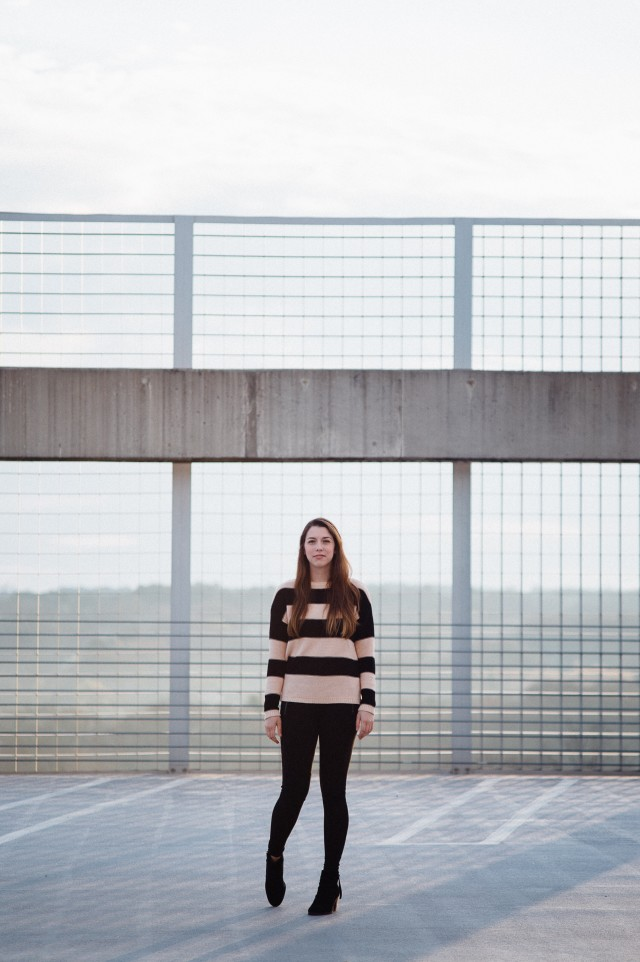 Girl standing on top of parking deck.