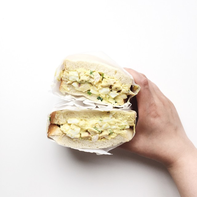Hand holding homemade chicken and egg salad sandwich
