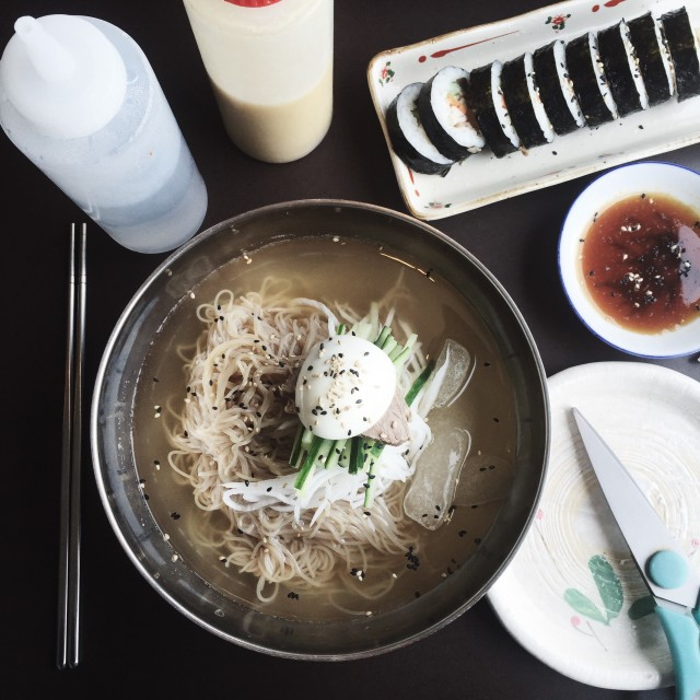 Bowl of Korean noodles naengmyeon and rice roll