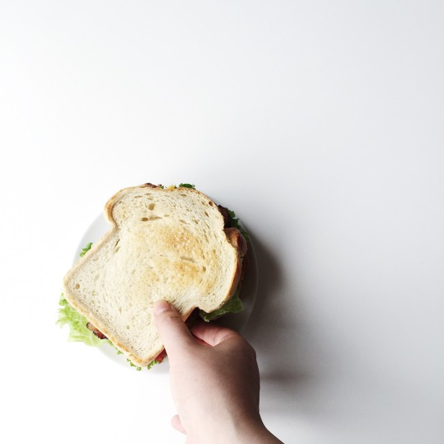 Hand picking up sandwich against white background