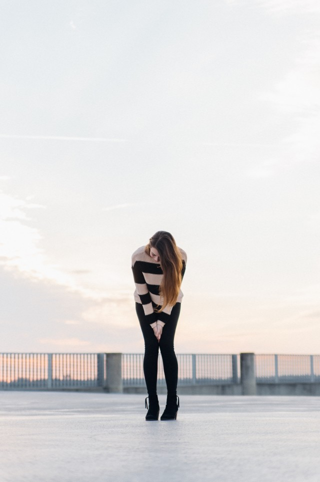 Young woman leaning forward on her knees standing on top of a parking deck.