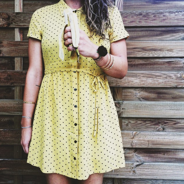 A girl wearing a yellow dress and holding a banana