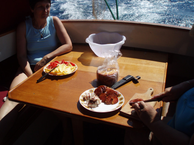 People Having Breakfast At Table In Boat