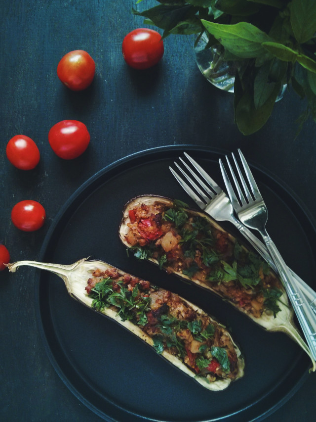 Baked eggplant with tomato cherry on dark wooden background