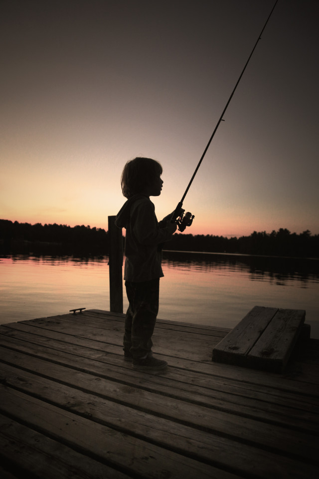 Child, fishing at dawn on the lake.