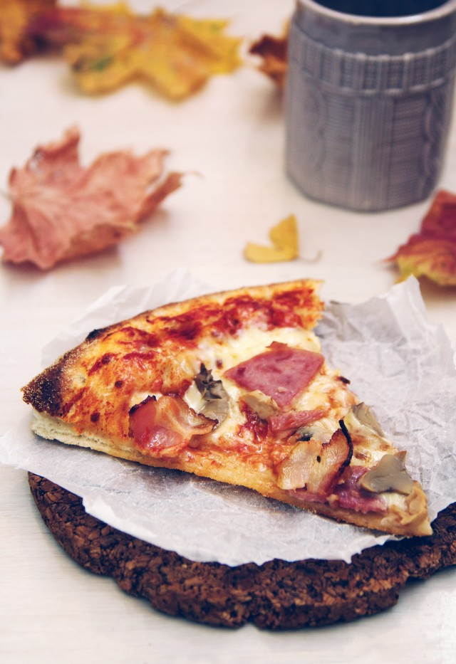 a piece of delicious pizza with tomatoes, cheese, ham and mushrooms on a background of autumn foliage