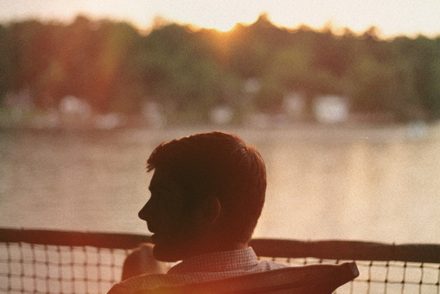 Young man sitting by lake during sunset.