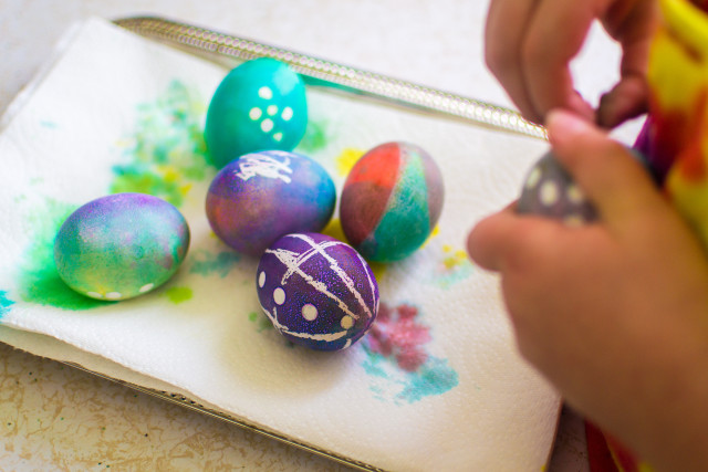 Hand dyed boiled eggs made by kids for Easter, patterns were made by using candle stick was and little round stickers. 5 year old is removing some of the stickers that were used as a mask to stop the dye from coloring the egg.