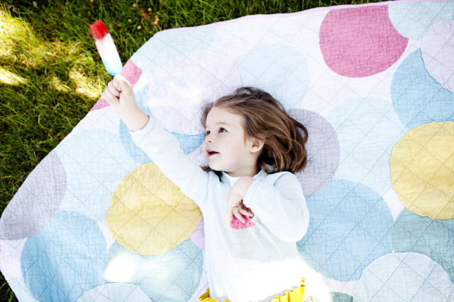 girl eating a Popsicle outside on a blanket