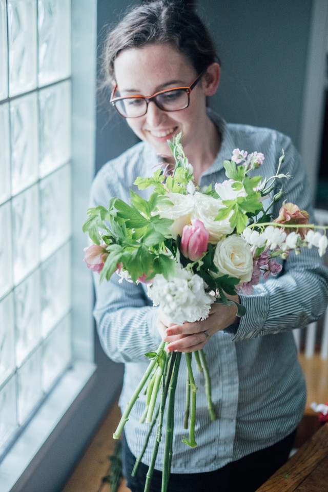 Woman makes a flower bouquet by a window in natural light