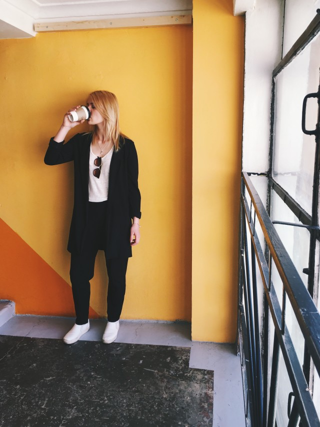Young business woman drinks coffee.