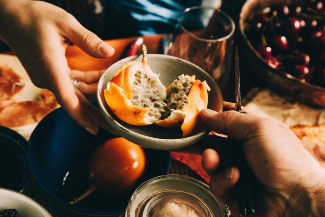 Passing a bowl of fruit at table, picnic table