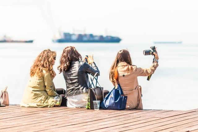 Young Girls Friends Taking Selfie And Using Mobile Phones At The Dock