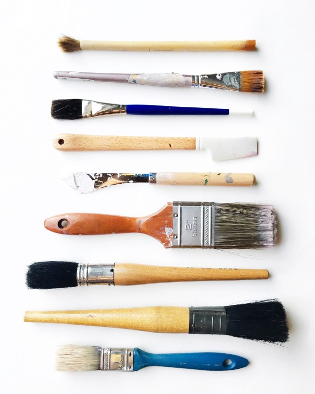 Collection of clean paintbrushes with wooden handles arranged in a neat pattern on a white background.