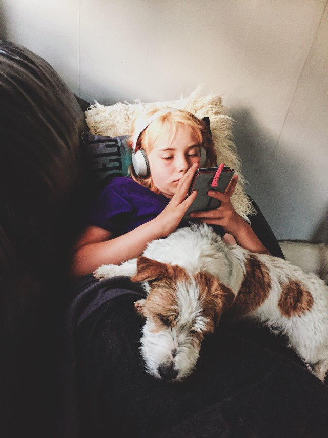 Girl using her phone with a dog in her lap