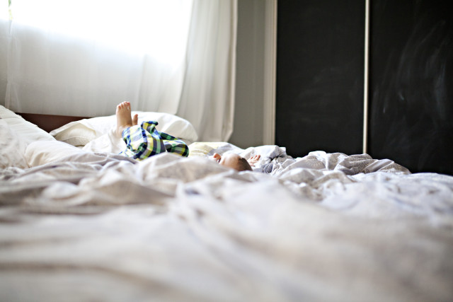 little boy lying on a bed after jumping