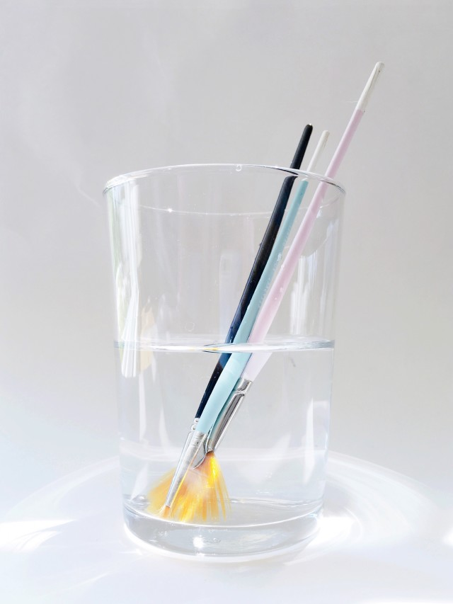 Assortment of colorful artist's paintbrushes leaning in a clear drinking glass of clean water against a white background.