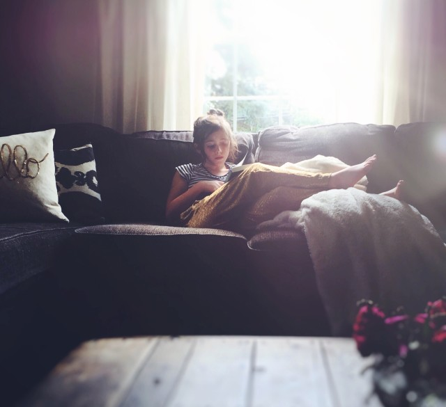 Young girl, on sofa reading in golden light.
