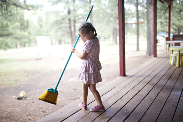 Girl sweeping porch at cabin