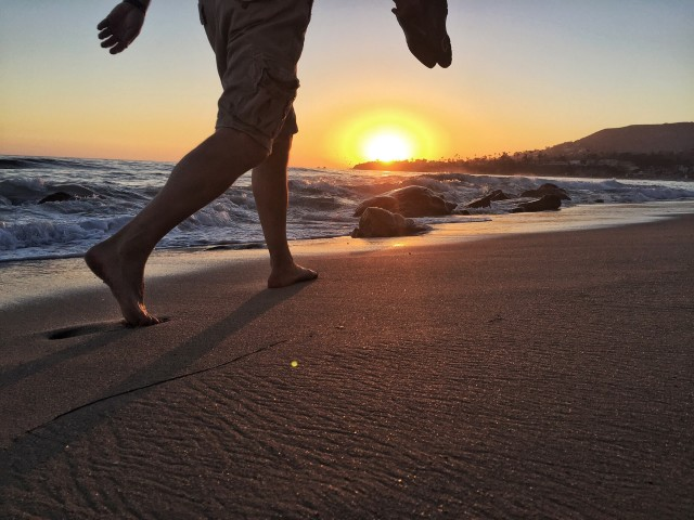 Man walking on the southern California beach at sunset