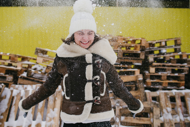 Young girl playing with snow. Happy wintertime
