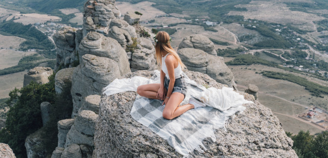 Young girl sitting on the top of Crimean rock
