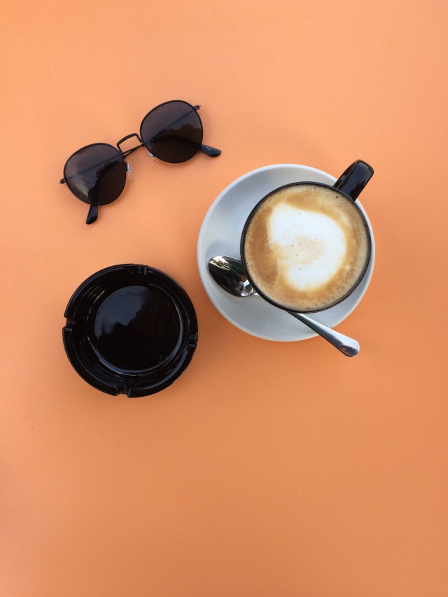 Sunglasses, black cup of coffee with spoon on Orange background.