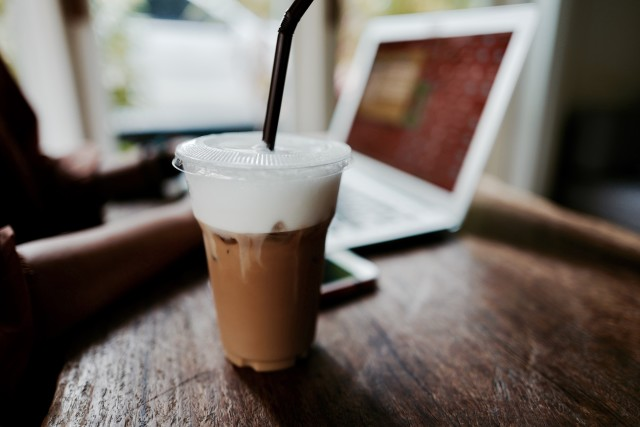 Iced coffee on wooden table with notebook at background