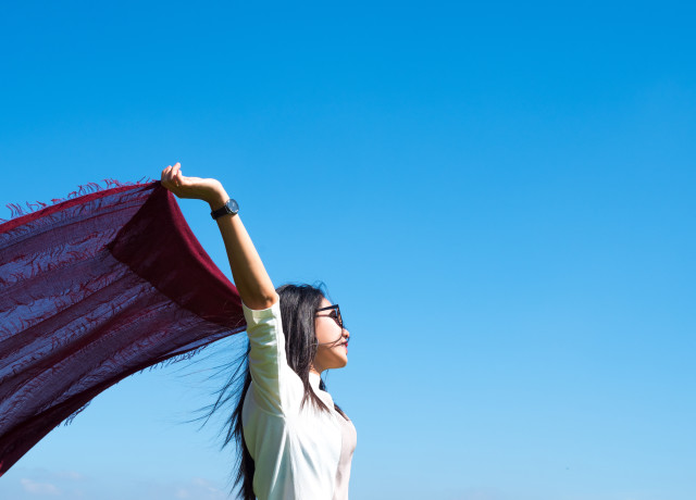 Asian woman with scarf against blue sky background enjoying nature, woman freedom concept.