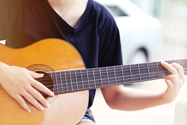 Young teenage girl playing guitar relaxing outdoor space