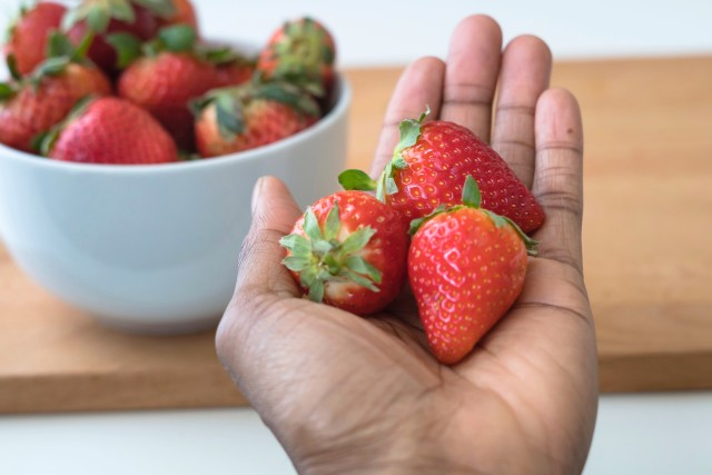 Open hand with strawberries and a bowl of strawberries in background
