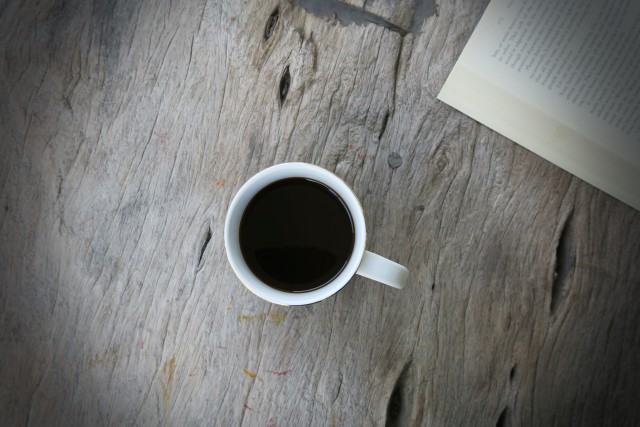 Cup of coffee with open book top view