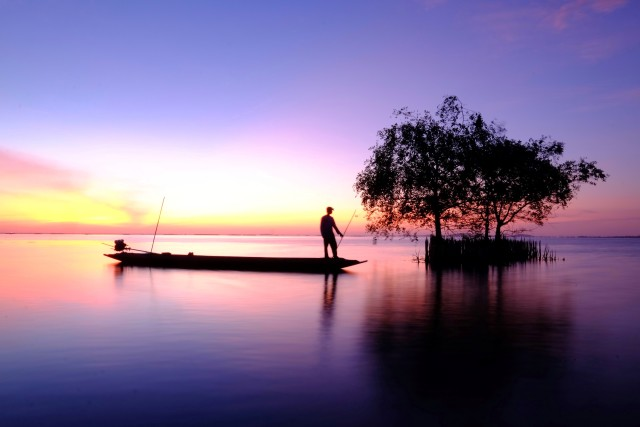 Fisherman standing in his boat in the sea at dawn