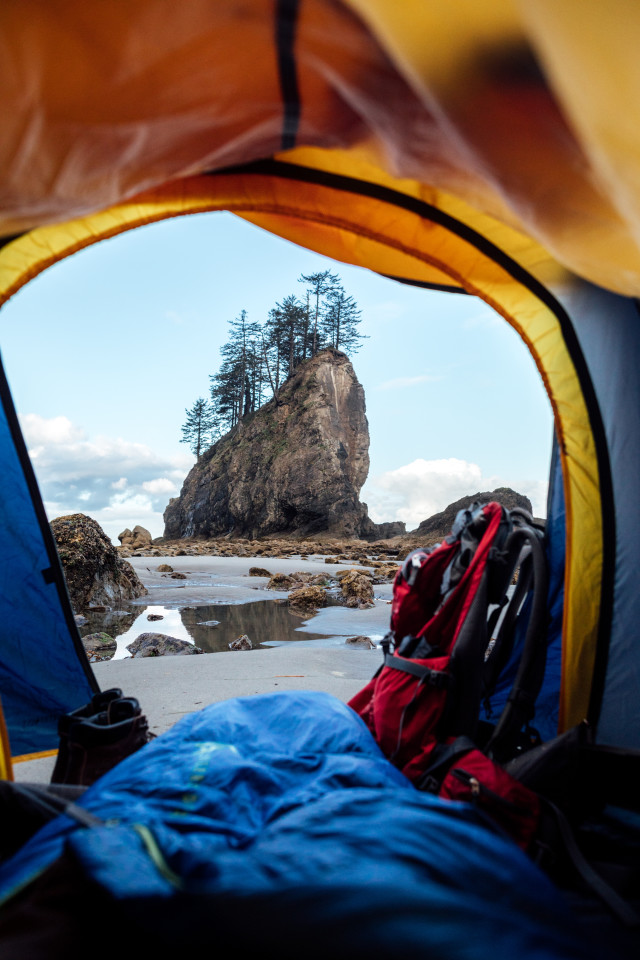 Looking out a tent, over a sleeping bag, boots, backpack and looking out at sunrise on the washington coast