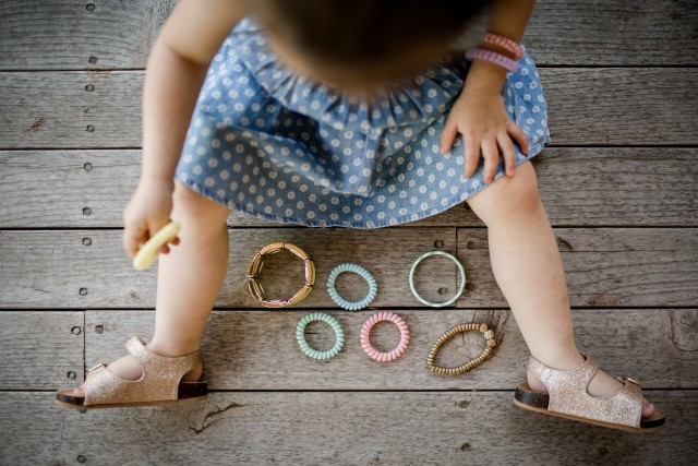 Toddler girl organizing her bracelets.