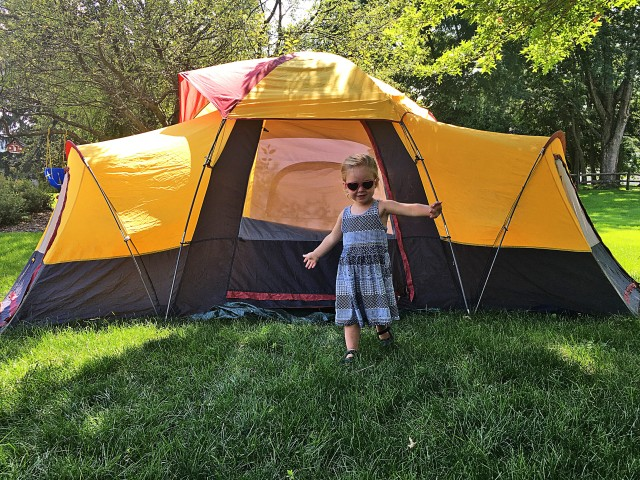 Toddler girl standing in front of a camping tent in summer.