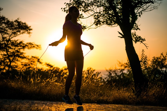 Silhouette of Girl jumping over a rope in sunrise light
