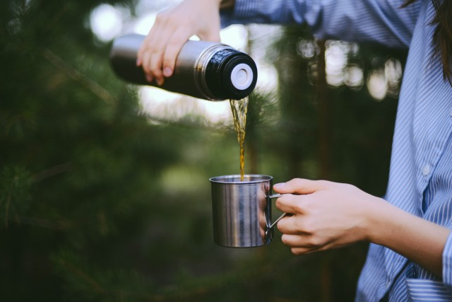 Woman traveler hands holding cup of tea the outdoors