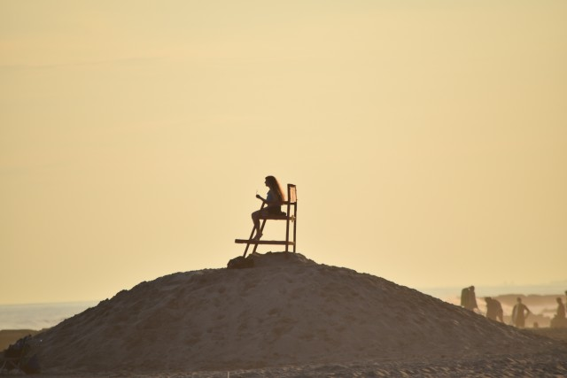Woman lifeguard guarding the beach at sunset -nominated