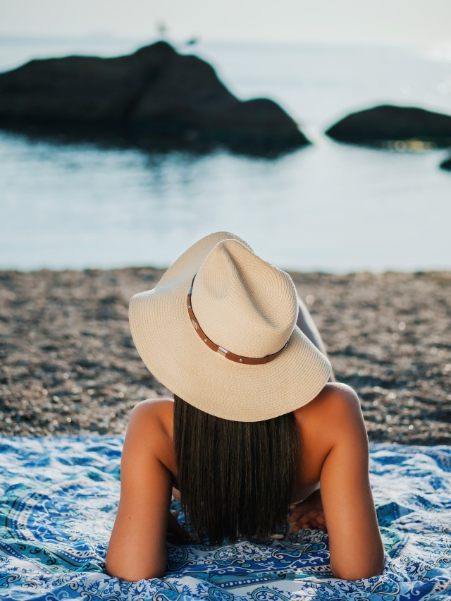 Girl in hat lying on beach near sea