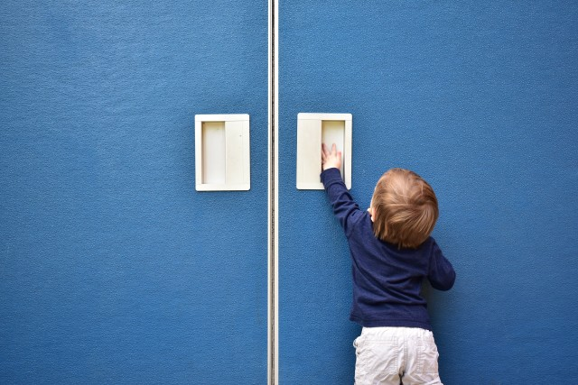 Cute baby boy trying to open blue door