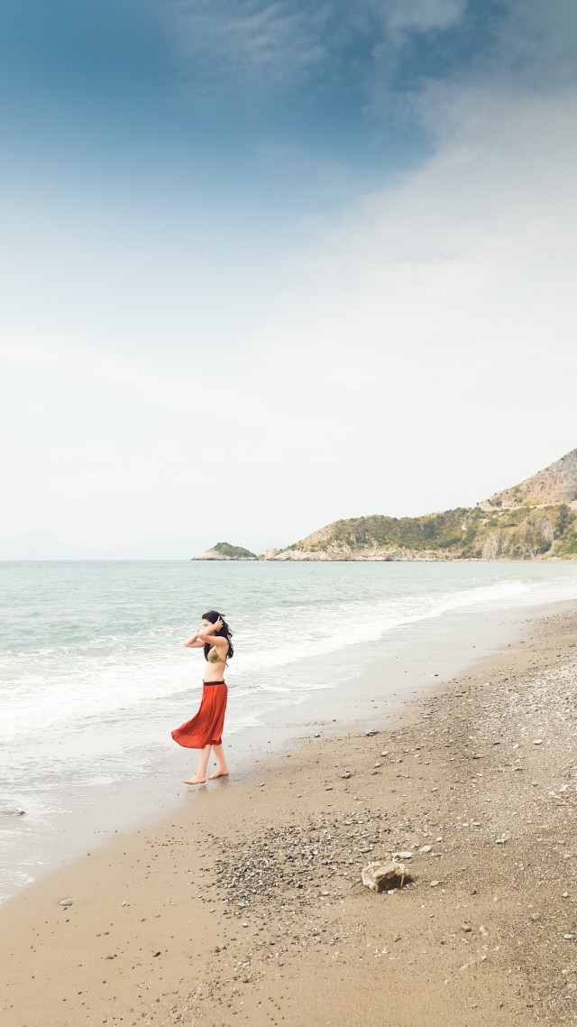 Young woman walking in barefoot on the seaside shore