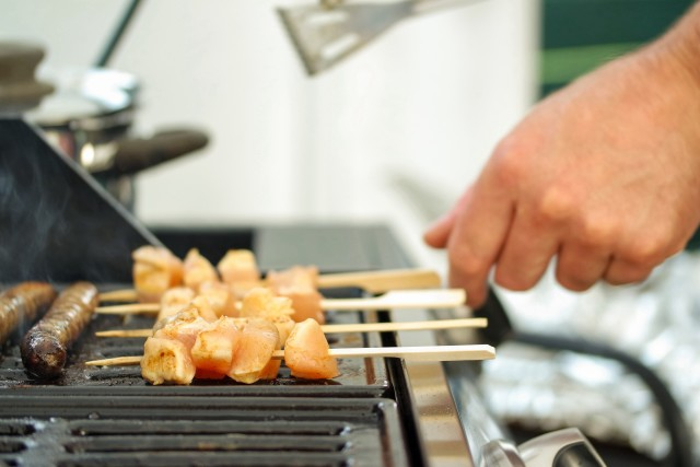 Close up of man grilling meat .  Close up of a hand.