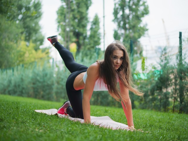 Sexy woman doing sport exercises in the park at summer