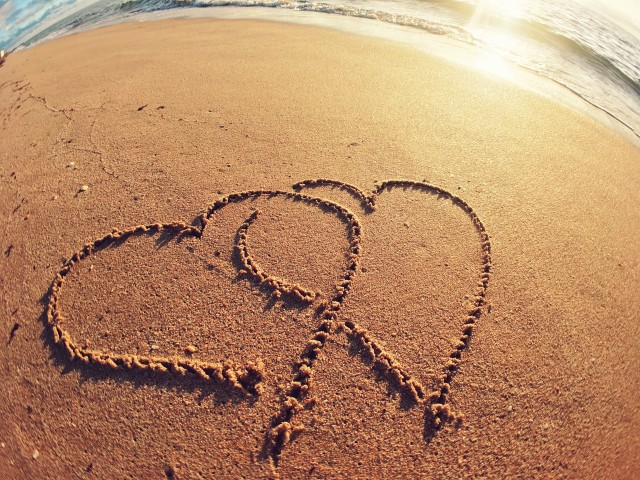 Two hearts interlocked in the sand