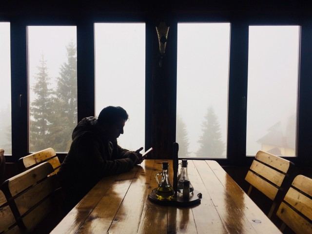 Single man in winter clothes texting at a table in a rustic restaurant with fog and trees seen out of the windows