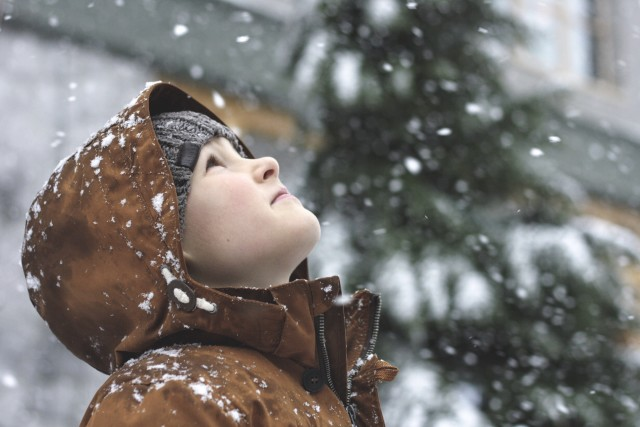 A boy marvels at falling snow